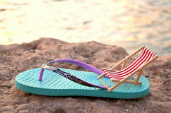Flipflop with beachchair. On a stone close up behind the sea royalty free stock image