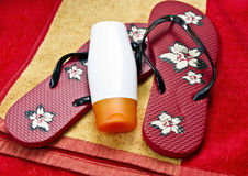 Flipflop and sunscreen on a beach towel Stock Photo
