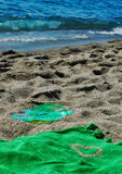 Flipflop and towel in the sand Royalty Free Stock Image