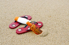 Flipflops And Sunscreen On The Beach Royalty Free Stock Photos