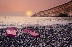 Flipflops auf dem Strand bei Sonnenuntergang Lizenzfreies Stockfoto