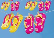 Flipflops auf Kleidungzeilen Stockfotos