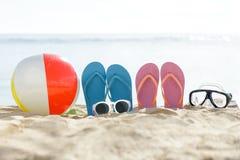 Flipflops, beach ball, sunglasses, and snorkel on the sand. Portrait of flipflops, beach ball, sunglasses, and snorkel on the sand Royalty Free Stock Photos