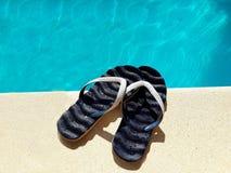 Flipflops durch den Swimmingpool Seashells gestalten auf Sandhintergrund lizenzfreies stockbild