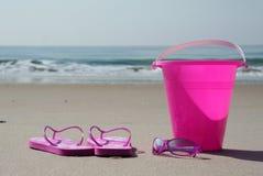 Flipflops, Farbtöne und Eimer auf dem Strand Stockfotos