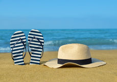 Flipflops and hat on a sandy ocean beach. Royalty Free Stock Images