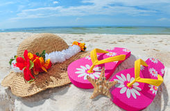 Flipflops and hat on shore Royalty Free Stock Image