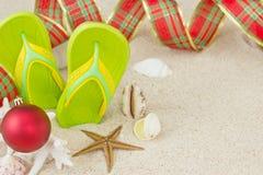 Flipflops im Sand und in der Weihnachtsdekoration Lizenzfreie Stockfotografie