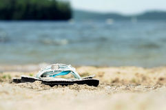 Flipflops by the lake. Isolated focus of flipflops on a sandy beach. Blurred lake, trees and mountain background stock photography