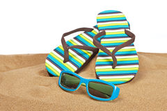 Flipflops on the sand. A pair of flipflops or beach sandals and sunglasses with copy space on a white background. Shallow depth of field stock image