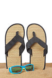 Flipflops on the sand. A pair of flipflops or beach sandals and sunglasses with copy space on a white background. Shallow depth of field royalty free stock image
