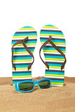 Flipflops on the sand. A pair of flipflops or beach sandals and sunglasses with copy space on a white background. Shallow depth of field stock photography