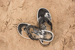 Flipflops on the sand. Black and white flipflops in the sand on the beach Royalty Free Stock Photography