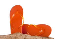 Flipflops in sand on white with copy space. Orange flipflops in sand on a white background with copy space royalty free stock image