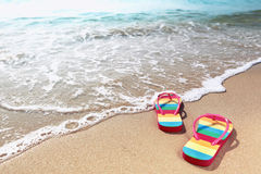 Flipflops on a sandy ocean beach Stock Photography