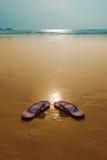 Flipflops on a sandy ocean beach Stock Photos