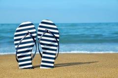Flipflops on a sandy ocean beach. Royalty Free Stock Image