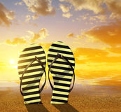 Flipflops on a sandy ocean beach. At sunset. Summer vacation concept Royalty Free Stock Photography