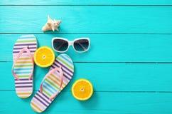 Flipflops, Sonnenbrille und Orangen auf blauem hölzernem Hintergrund Draufsicht- und Kopienraum Lizenzfreies Stockfoto
