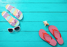 Flipflops, Sonnenbrille und Seeoberteil auf blauem hölzernem Hintergrund Kopieren Sie Raum- und Modesommerzubehör Stockfoto