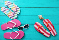 Flipflops, Sonnenbrille und Seeoberteil auf blauem hölzernem Hintergrund Kopieren Sie Raum- und Modesommerzubehör Lizenzfreies Stockbild