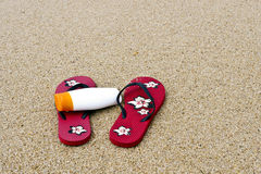 Flipflops and sunscreen on the beach Royalty Free Stock Photo