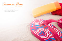 Flipflops ,sunscreen,towel on beach Stock Photography