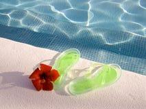 Flipflops am Swimmingpool Lizenzfreie Stockfotografie