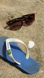 Flipflops und Sonnenbrille auf Sand Stockfoto