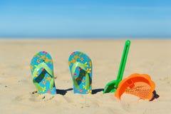 Flipflops und Spielwaren am Strand Lizenzfreie Stockfotos