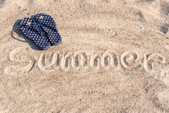 Flipflops with the word summer. Flipflops on beach, with the word summer written on sand royalty free stock photos