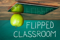 Flipped Classroom Concept. On Blackboard With Apple And Digital Tablet On Wooden Table Stock Photo