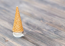 Flipped vanilla ice cream in a waffle cones. On wooden background royalty free stock photo
