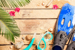 Flippers, goggles and snorkel on tropical beach. Summer holiday (vacation) tropical beach background layout with snorkeling theme and free text space. Flippers Stock Images