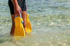 Flippers in the hands of a man on the Mediterranean coast royalty free stock image