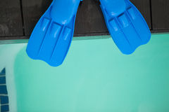 Flippers hanging over edge of pool Royalty Free Stock Photography