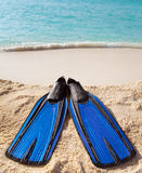 Flippers lay on sand on background of ocean Royalty Free Stock Photography