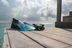 Flippers and mask on a pier with cloudy sky as background stock photo