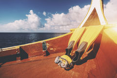 Flippers and swimming mask on deck of boat. Yellow fins and swimming mask laying on bottom of diving boat next to stern on warm sunny summer day with Indian Stock Photography