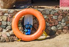 Flippers with swimming mask and an orange life preserver against a stone wall in Egypt stock images