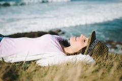 Flippige Frau, die in Richtung zum Meer stillsteht und sich entspannt Stockfoto