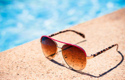 Flippige Sonnenbrillen Browns nähern sich Swimmingpool Stockbild