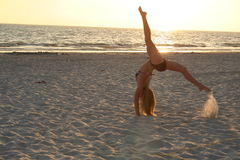 Flipping. Female gymnast doing a backflip on the beach Stock Photography