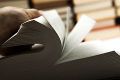 Flipping book on with pile of books. Close up Royalty Free Stock Photo