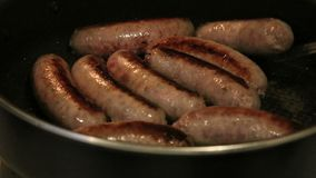 Flipping brats over in pan. Brats frying in cast iron skillet stock video footage