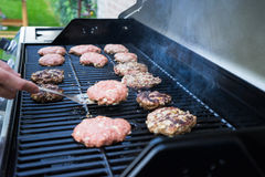 Flipping Burgers on a Grill Stock Image