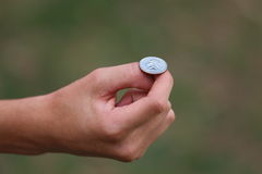 Flipping a Coin. A close up view of someone about to flip American currency Stock Photo