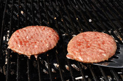 Flipping Hamburgers on the Grill Stock Photos
