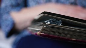Flipping through an old photo album. An old woman is browsing an old photo album. Closeup of hands and album stock video