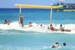 Flips för utriggarekanot över i den Waikiki stranden Arkivfoto